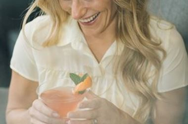 Woman with cocktail smiling