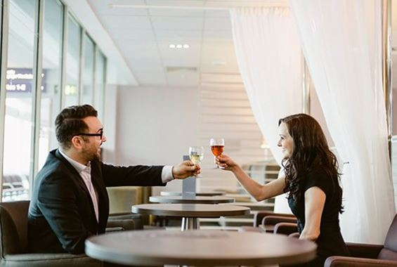 Woman and man toasting with drinks in lounge
