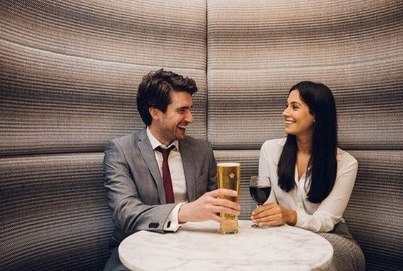 Woman drinking with man in lounge booth